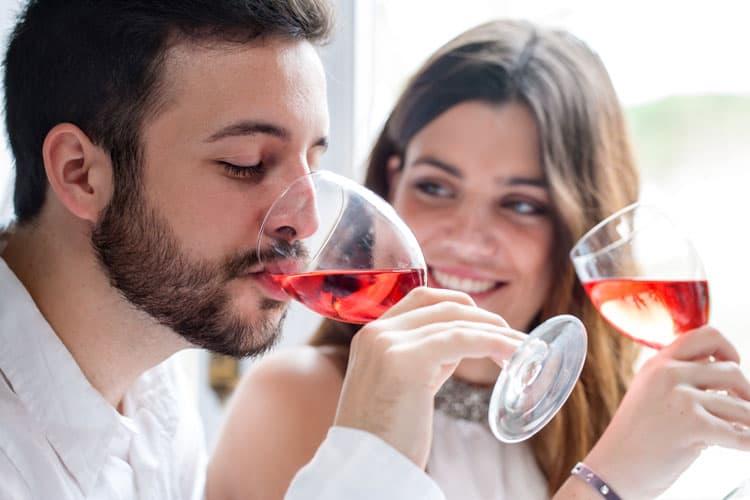 Man proeft wijn, vrouw kijkt toe.